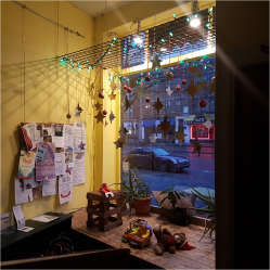image is the Coop's front window, with kid's toys and hanging floral origami, looking out on a rainy street at night